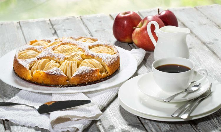 Apple pie, coffee cup and plate, apples on wood