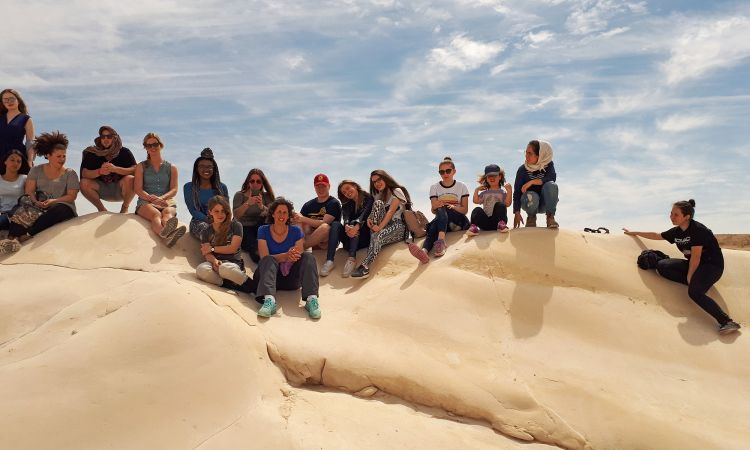 while German pupils climb rock formations in the Negev Desert