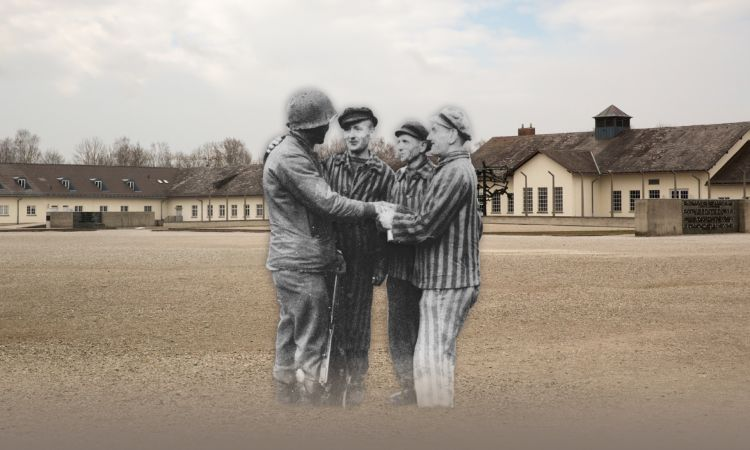 Prisoners support each other in front of the barracks of Dachau concentration camp.